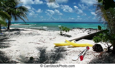 Ocean on background of bright yellow canoe under palm trees...