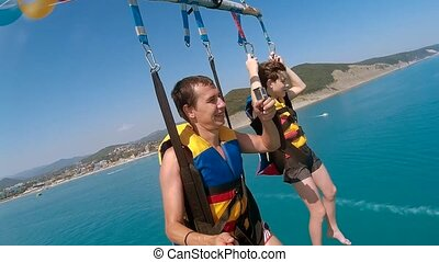 ocean paragliding and parasailing lifestyle. man and boy are...