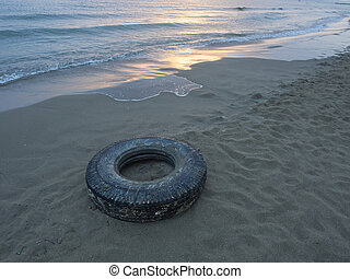 ocean plastic pollution: old truck tyre (tire) on the beach