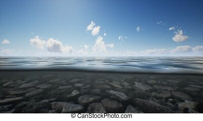 ocean seascape with sky and ocean wave splitted by waterline to underwater part