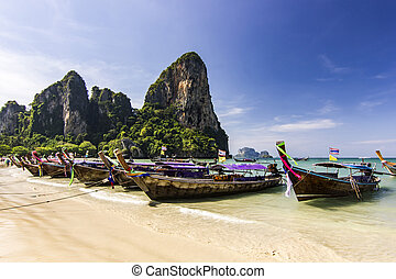 ocean seashore with island and boat on water at sunset in Krabi, Thailand