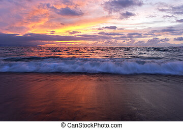 Ocean sunset landscape is beautiful colorful cloud filled sunset sky with a gentle white wave rolling to the shore.