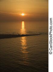 Sunset over ocean with breakwater.