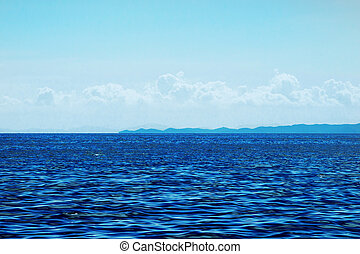 ocean surface and blue sky with clouds with mountain view