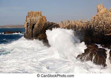 powerful waves splashing on rocky coastline, ouessant island, brittany, france