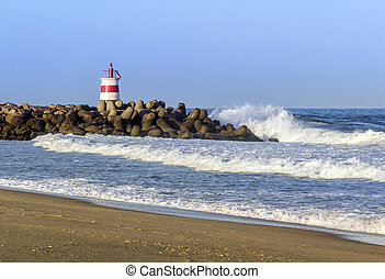 Ocean view and small lighthouse in the inlet jetty of Tavira Island, Algarve, Portugal.