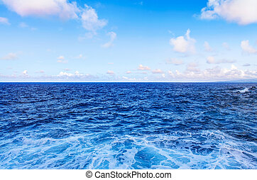 Ocean water waves and blue sky with white clouds.