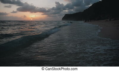 Ocean Waves and Amazing tropical Beach with beautiful mountains on Bali at sunset