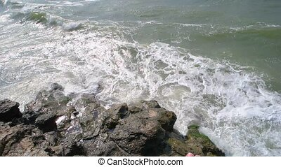 Ocean waves bite rocky coast. Danger waves.