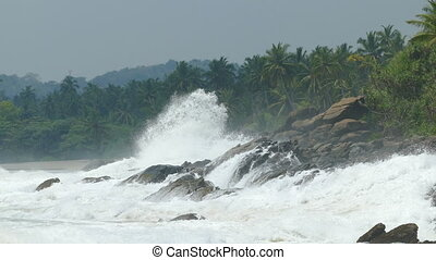 ocean waves breaking on rocks of tropical coast