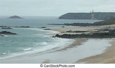 Ocean waves crash along sand beach