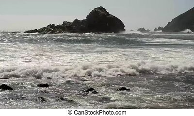Ocean waves crashing against rocks at Big Sur California as...