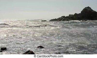 Ocean waves crashing against rocks at Big Sur California as...