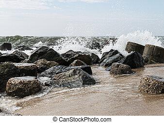 Ocean waves crashing in to rocks on shore
