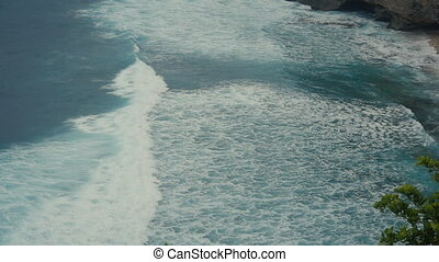 Ocean waves move to shore. Aerial top view of Tropical beach Bali, Indonesia. Slow motion