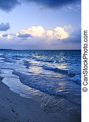 Ocean waves on beach at dusk with sunlit clouds