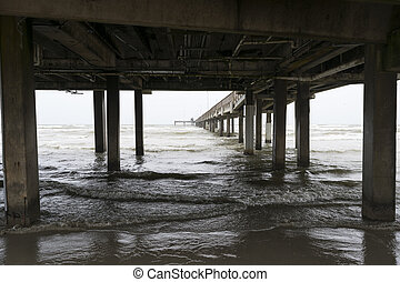 Ocean waves rolling onto the beach under a long pier