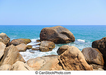 ocean waves wash the rocks of a tropical beach