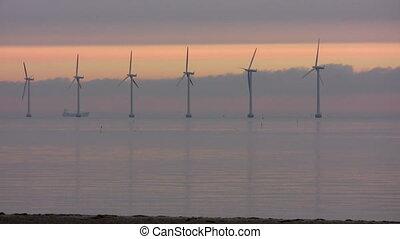 Ocean wind turbines af dawn - Huge ocean wind turbines at...