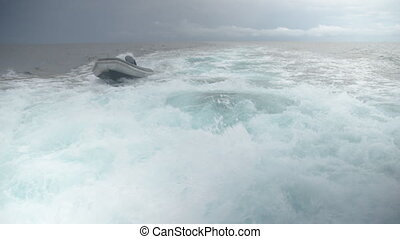 Ocean with mini boat - A Wide shot of ocean gushing with...