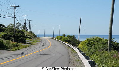 Car goes past on road beside the sea. Saint John, New Brunswick.