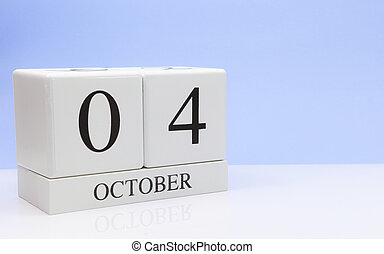 October 04st. Day 4 of month, daily calendar on white table with reflection, with light blue background. Autumn time, empty space for text
