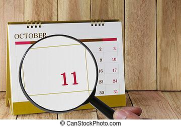 october., konzerv, nagyító, hónap, naptár, szám, ön, néz, dátum, kéz, összpontosít, eleventh, tizenegy