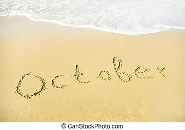 october - October - written in sand on beach texture