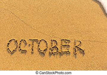 October - written on sandy beach.