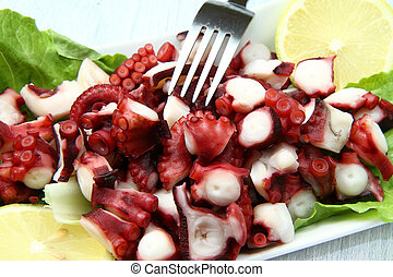 octopus salad with lemon slice and lettuce