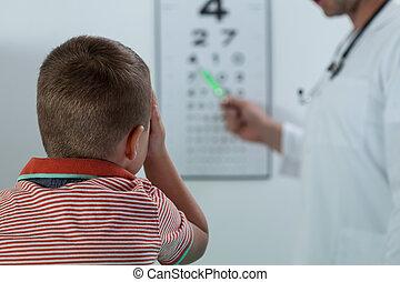 Oculist examining boy vision