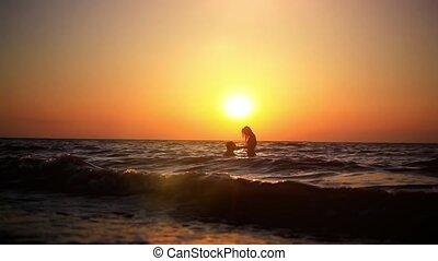 odbijanie się, para, przeciw, water., sylwetka, bryzgany, turysta, brzeg, pływacki, sunset., słońce, zdumiewający, fale, ferie, odbicia, pojęcie, piękny