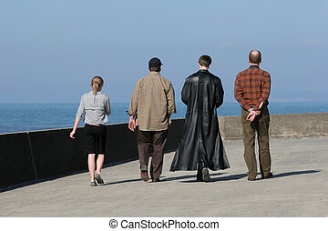 Odd One Out - Rear view of four people walking on a seaside ...