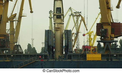 ODESSA - MAY 28: Port cranes loading dry-cargo ship on May 26, 2013 in Odessa, Ukraine. Odessa port is one of the biggest ports located on the Black Sea coast.