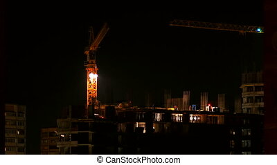 ODINTSOVO, RUSSIA - October 20, 2015. Timelapse clip of building construction at night. Workers in orange uniform build an apartment building. Construction crane moves from one side to another.
