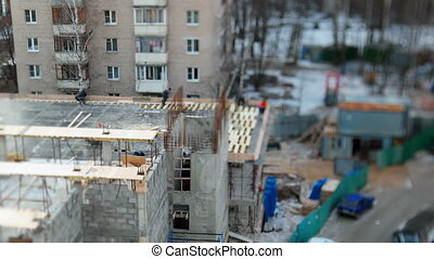 ODINTSOVO, RUSSIA - October 20, 2015. Timelapse clip of building construction. Workers in uniform build an officce building. Tilt-shift lens blur effect.
