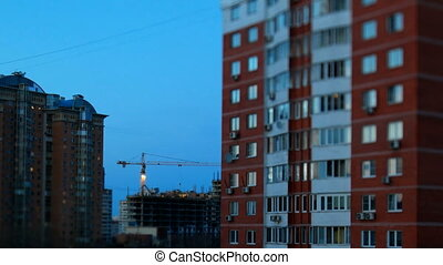 ODINTSOVO, RUSSIA - October 20, 2015. Timelapse tilt-shift clip of building construction. Workers in orange uniform build an apartment building.