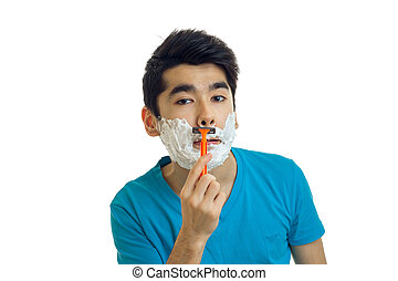 of a handsome young man with foam on his face shaves his beard and looks into a camera