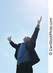 Of course! - Business man raising his hands up to the sky as...