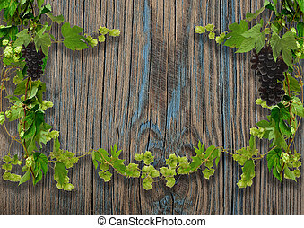 of wild grapes and hop leaves on a wooden wal with copy space