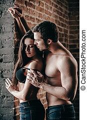 oferta, y, sensual., vista lateral, de, hermoso, joven, shirtless, pareja, en, vaqueros, vinculación, a, uno al otro, mientras, hombre, lejos, sostén, de, el suyo, novia
