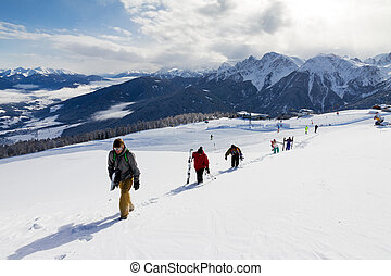 Off-piste hiking - Group of skiers and snowboarders hiking...