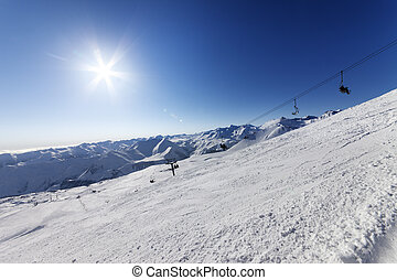 Off-piste slope and blue sky with sun. Caucasus Mountains,...