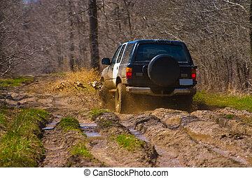 Off-road car going through deep mud holes