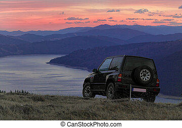 off road car in the mountain landscape and lake