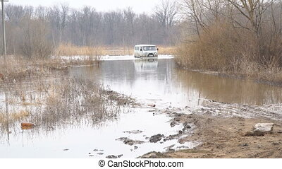 Off-road car is wading through a spilled river - An off-road...