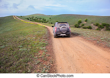 off-road car moves along a dirt mountain road