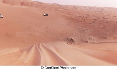 Off-road cars with tourists descend from a high dune in Rub...