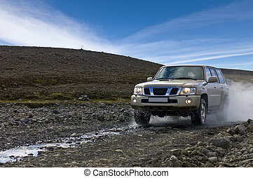 Off Road Driving - A big four by four car, emerging from a...
