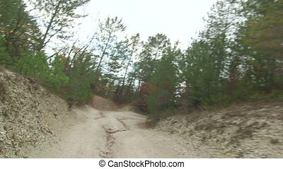 Off-road driving on rutted dirt track in mountains